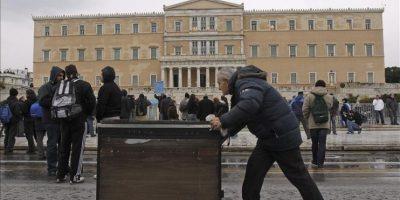 Un vendedor ambulante empuja un carrito durante una manifestación convocada por los dos sindicatos mayoritarios griegos (GSEE y ADEDY) para protestar contra los recortes de las pensiones y el cambio de la legislación laboral, en la plaza Sintagma frente al Parlamento griego en Atenas, Grecia, hoy, miércoles 22 de febrero de 2012. EFE