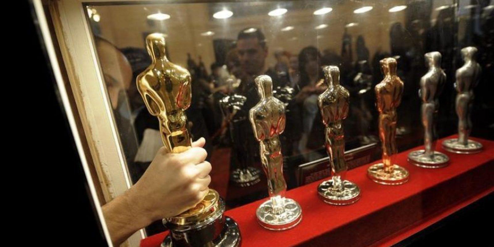 Un operario coloca un premio Oscar durante la apertura de la exposición que mostrará algunas de las estatuillas de los premios Oscar de Hollywood que se entregarán en su 84 edición, en Nueva York, Estados Unidos. EFE