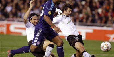 Los jugadores del Valencia el turco Mehmet Topal (i) y el español Ángel Dealbert (d) intenta evitar un ataque del delantero inglés del Stoke inglés Cameron Jerome, durante el partido de vuelta de los dieciseisavos de final de la Liga Europa que disputaron en el estadio de Mestalla. EFE