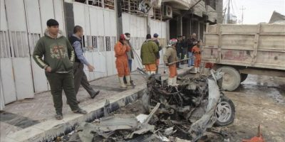 Operarios retiran los restos del coche bomba que ha explotado frente a un punto policial de la ciudad iraquí de Samara, dejando un muerto y otras cinco personas heridas de diversa consideración. EFE