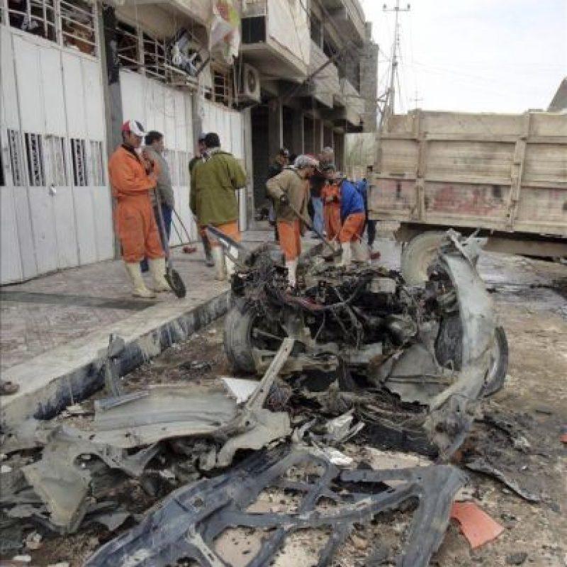 Operarios retiran los restos del coche bomba que ha explotado frente a un punto policial de la ciudad iraquí de Samara, dejando un policía ha muerto y otras cinco personas heridas de diversa consideración. EFE