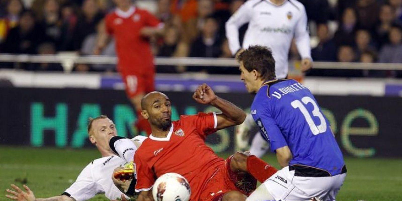 El delantero malí del Sevilla FC Frederic Kanouté (c) pelea en el suelo por el balón con el defensa y el portero del Valencia CF Jeremy Mathieu (i) y Vicente Guaita, respectivamente, durante el partido, correspondiente a la vigésimo quinta jornada del Campeonato Nacional de Liga de Primera División, que han disputado ambos equipos en el estadio de Mestalla. EFE