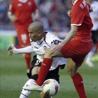 El centrocampista argelino del Valencia CF Sofiane Feghouli (i) pugna por el balón con el defensa del Sevilla FC Fernando Navarro durante el partido, correspondiente a la vigésimo quinta jornada del Campeonato Nacional de Liga de Primera División en el estadio de Mestalla. EFE