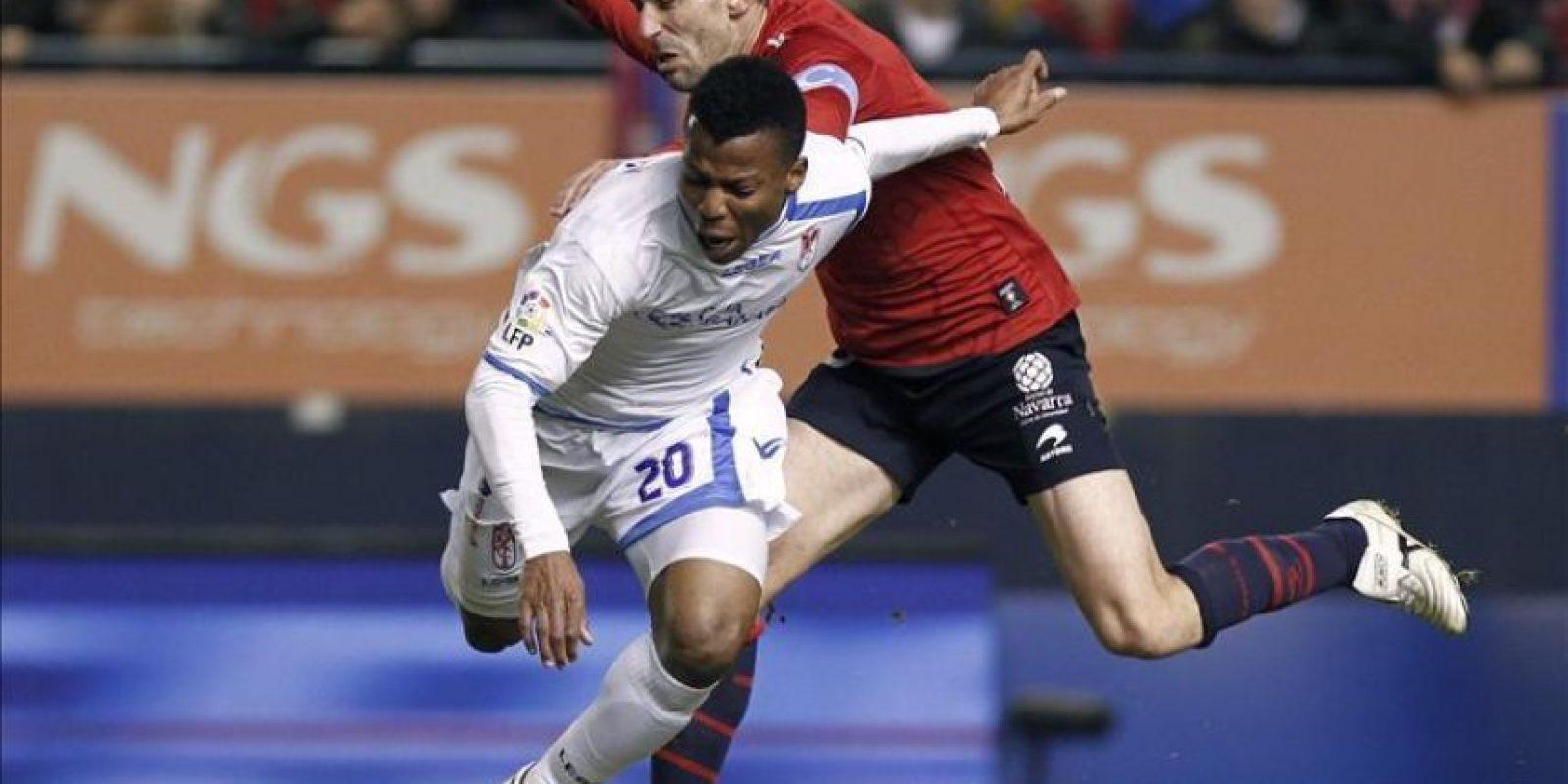 El delantero nigeriano del Granada CF Ikechuwku Uche (i) cae ante la entrada del centrocampista de Osasuna Patxi Puñal durante el partido, correspondiente a la vigésimo quinta jornada del Campeonato Nacional de Liga de Primera División, que han disputado ambos equipos en el estadio Reyno de Navarra. EFE