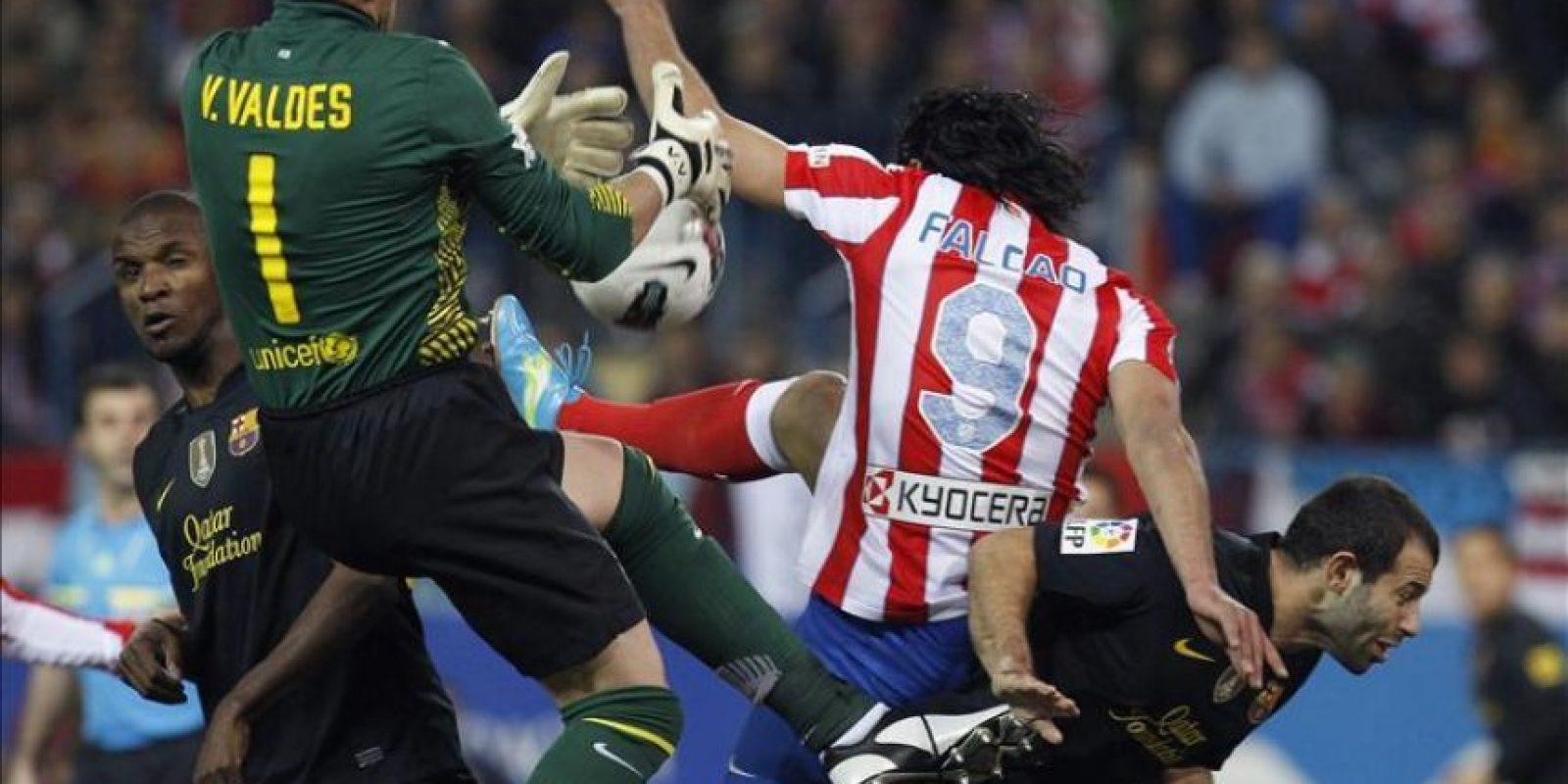 El portero del FC Barcelona Víctor Valdés (2i) no consigue atajar un balón ante la presencia del delantero colombiano del Atlético de Madrid Radamel Falcao (2d) durante el partido, correspondiente a la vigésimo quinta jornada del Campeonato Nacional de Liga de Primera División en el estadio Vicente Calderón. EFE