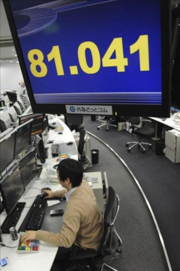 Un empleado trabaja de bajo una pantall que muestra la evolución del dólar frente al yen en Tokio, Japón. EFE