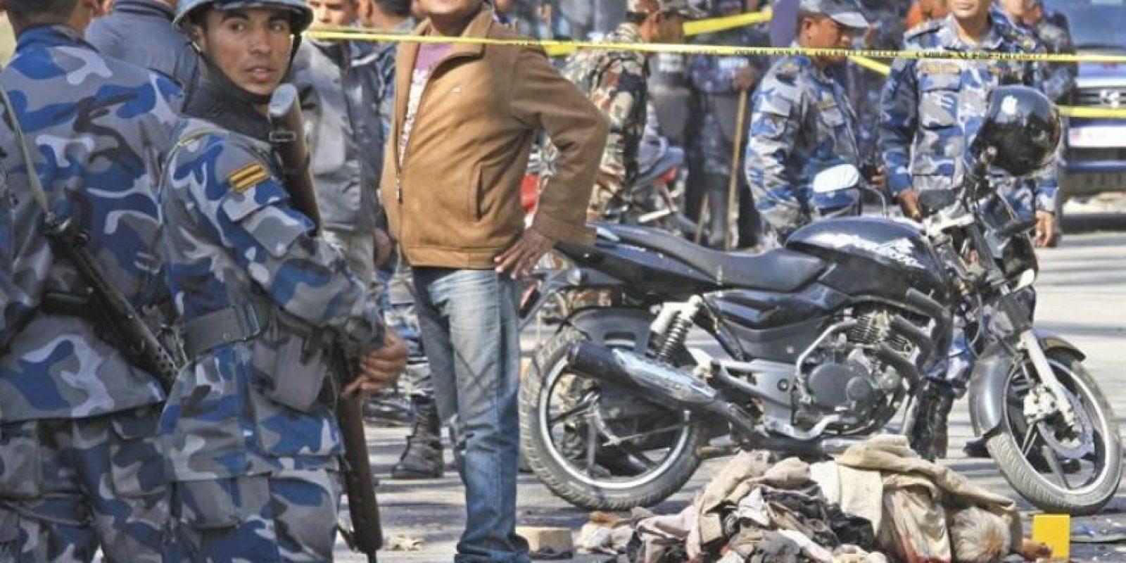 Efectivos de la policía examinan el cadáver de una víctima de un atentado ante las oficinas de la compañía petrolífera Nepal Oil Corporation en Katmandú, Nepal, el lunes 27 de febrero de 2012. EFE
