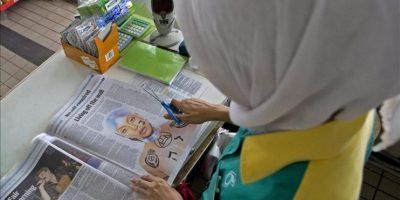 """Una mujer musulmana recorta una fototgrafía de la cantante estadounidense Erykah Badu en la que aparece con varios tatuajes, incluyendo el símbolo para """"Allah"""" (Dios), en Kuala Lumpur, Malasia, el martes 28 de febrero de 2012. La foto, publicada el día anterior por el periódico malasio The Star, provocó la ira de religiosos islámicos en el país y la cancelación de su concierto en Kuala Lumpur previsto para el 29 de febrero de 2012. EFE"""