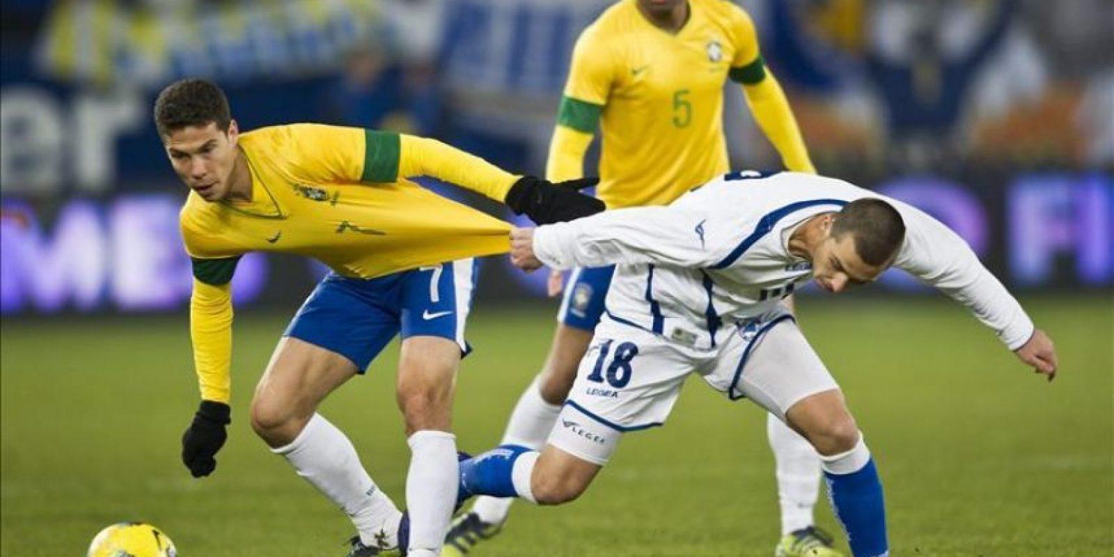Hernanes (i), de la selección brasileña lucha por el balón con Haris Medunjanin (d), de la selección Bosnia, durante el partido amistoso que ambas selecciones juegan en el AFG Arena de St. Gall, Suiza.EFE