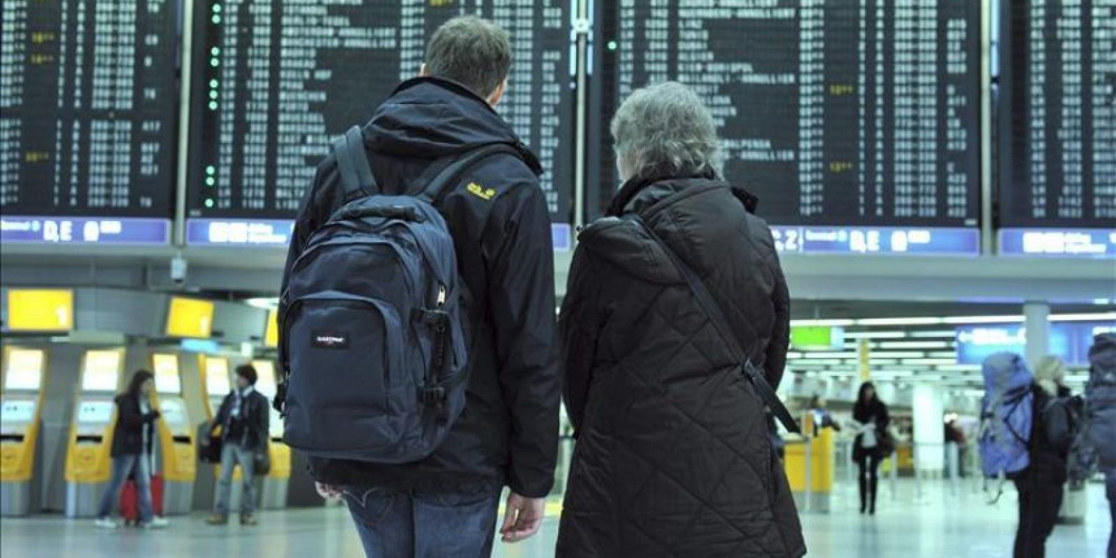 Dos viajeros buscan hoy información de sus vuelos en los paneles informativos dispuestos en el vestíbulo del aeropuerto internacional de Fráncfort (Alemania). La huelga de los controladores de tierra continúa hoy en el aeropuerto internacional alemán de Fráncfort, el mayor del continente, donde se ha anunciado la cancelación de unos 230 vuelos de los cerca de 1.300 previstos. EFE