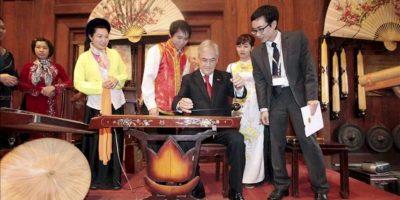 El presidente chileno, Sebastian Piñera (3ºdcha), intenta tocar un instrumento tradicional vietnamita tras escuchar un concierto durante su visita al Templo de la Literatura hoy, 22 de marzo de 2012, en Hanoi (Vietnam). EFE