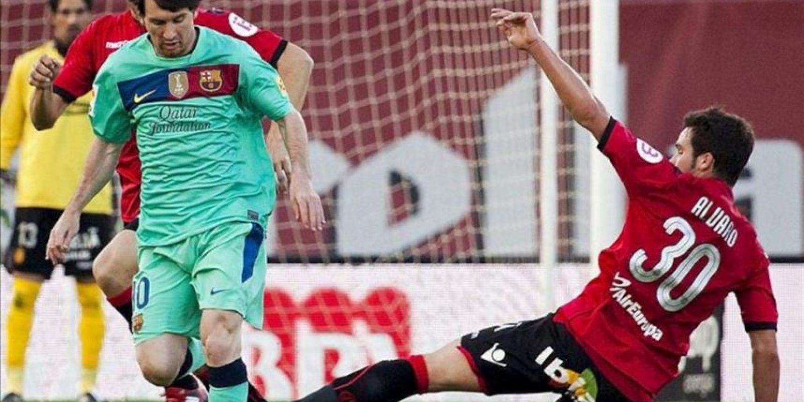 El delantero del RCD Mallorca Alvaro Giménez (d) pelea un balón con el delantero argentino del FC Barcelona Lionel Messi, durante el partido de futbol correspondiente a la trigésima jornada de liga en Primera División en el Iberostar Estadio. EFE