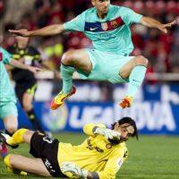 El defensa del FC Barcelona Martín Montoya salta por encima del portero el RCD Mallorca, el israelí Dudu Aouate, en el partido correspondiente a la trigésima jornada de liga en Primera División, disputado en el Iberostar Estadio. EFE