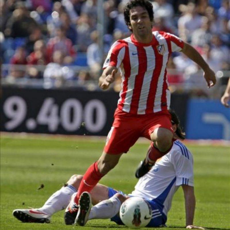 El centrocampista croata del Real Zaragoza, Tomislav Dujmovic (detrás) es superado por el centrocampista turco del Atlético de Madrid, Arda Turan, en su partido correspondiente a la trigésima jornada de Liga en Primera División que se ha disputado esta mañana en el estadio de la Romareda. EFE
