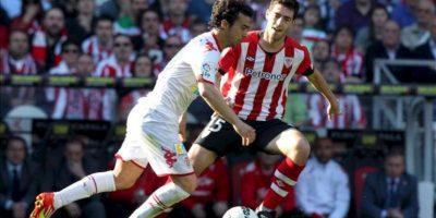 El defensa del Athletic de Bilbao Andoni Iraola (d) pugna por un balón con el centrocampista del Sporting de Gijón Miguel de las Cuevas durante el partido, correspondiente a la trigésima jornada de Liga de Primera División en el estadio de San Mamés. EFE
