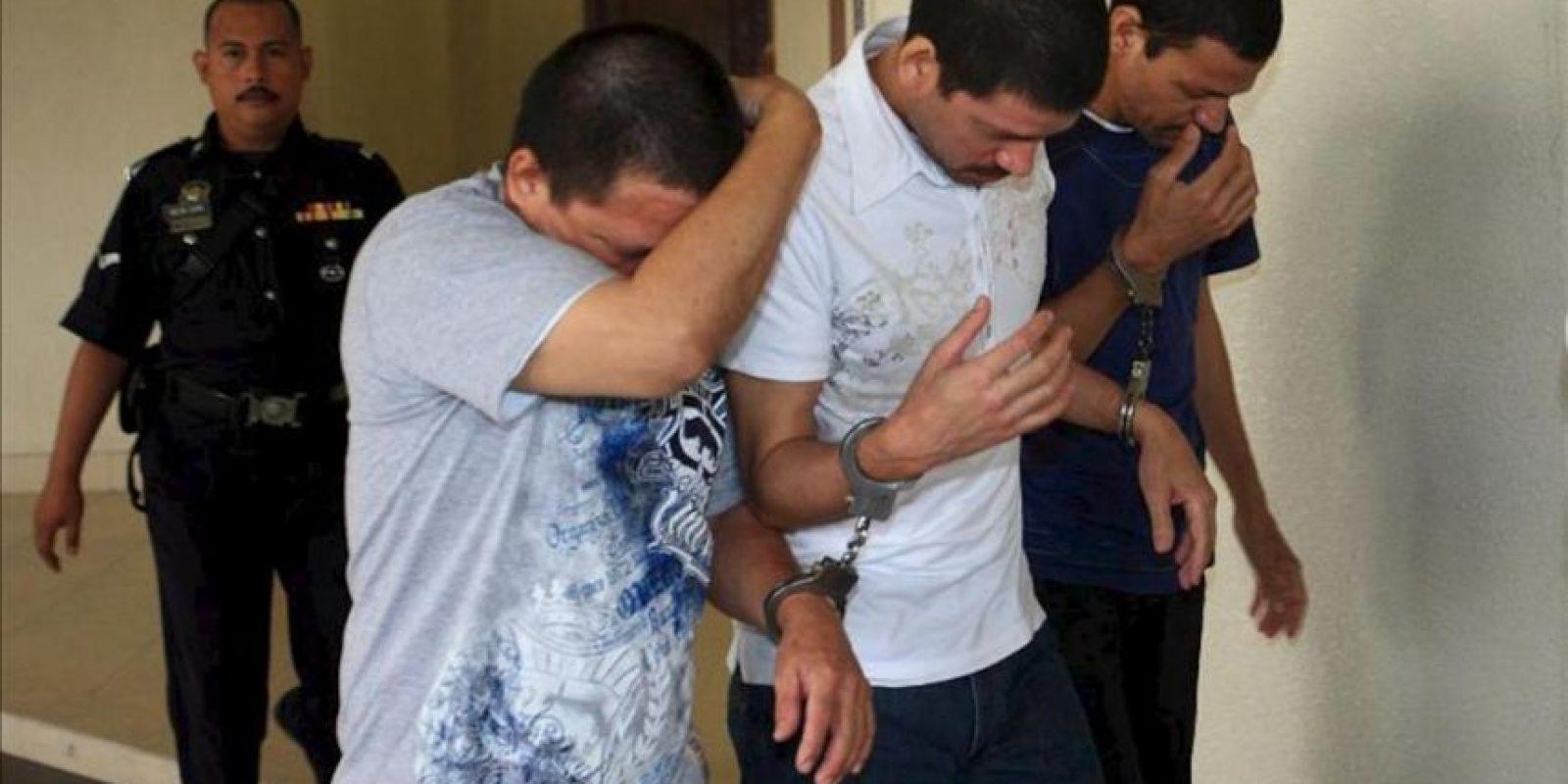Un policía malayo escolta a los hermanos mexicanos Luis Alfonso González Villareal (i), Simón González Villareal (c) y José Regino González Villareal (d) a su llegada este, lunes 26 de marzo de 2012, a un juzgado después de un receso en Kuala Lumpur (Malasia). EFE