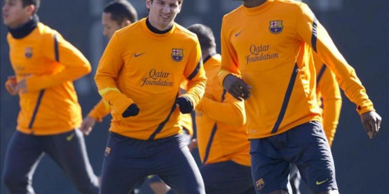 Los jugadores del FC Barcelona Leo Messi (i) y Eric Abidal (d) hacen ejercicios de calentamiento durante un entrenamiento del equipo culé. EFE/Archivo