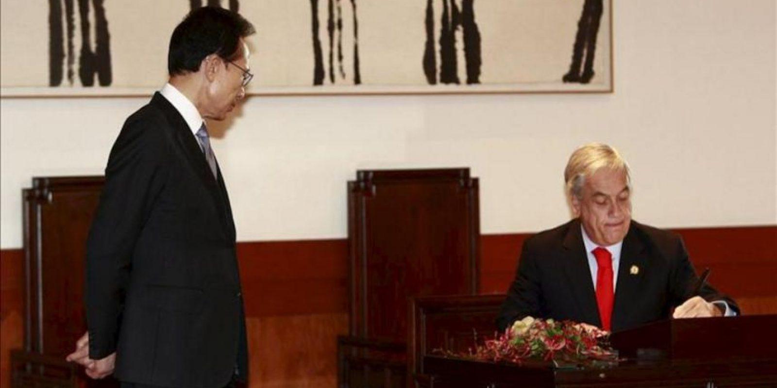 El presidente de Chile, Sebastián Piñera (d), firma un documento junto a su homólogo surcoreano, Lee Myung-bak (i), hablan hoy en una reunión en el despacho presidencial surcoreano en Seúl (Corea del Sur). EFE