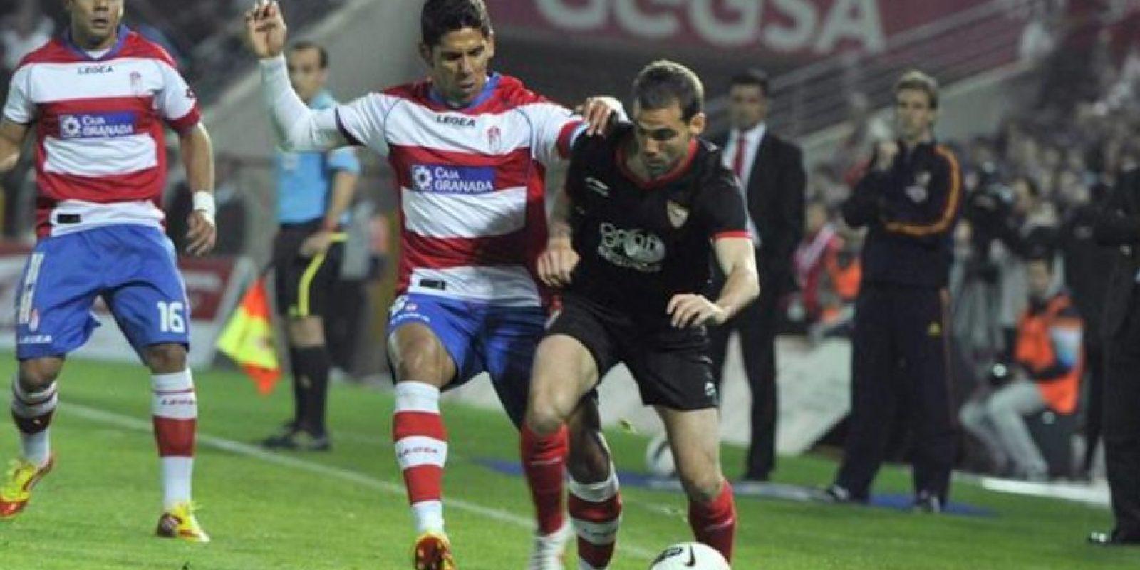 El delantero del Granada Franco Jara (c) pelea un balón con el delantero del Sevilla Alvaro Negredo (d), en su partido correspondiente a la trigésima jornada de liga en Primera División en el estadio de los Cármenes de la capital granadina. EFE