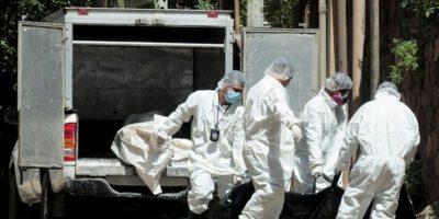 Empleados de medicina forense cargan el 18 de febrero de 2012, los cadáveres incinerados de los reos que murieron en penal de Comayagua. EFE/Archivo