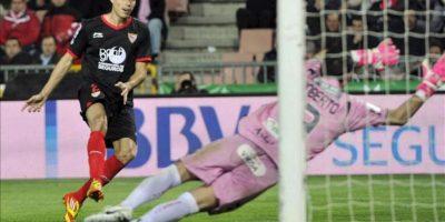 El delantero del Sevilla, Manu del Moral (i), golpea el balón ante el guardameta del Granada, Roberto, consiguiendo el tercer gol del equipo sevillista, durante el encuentro correspondiente a la jornada 30 de primera división, que han disputado en el estadio granadino de Los Carmenes. EFE