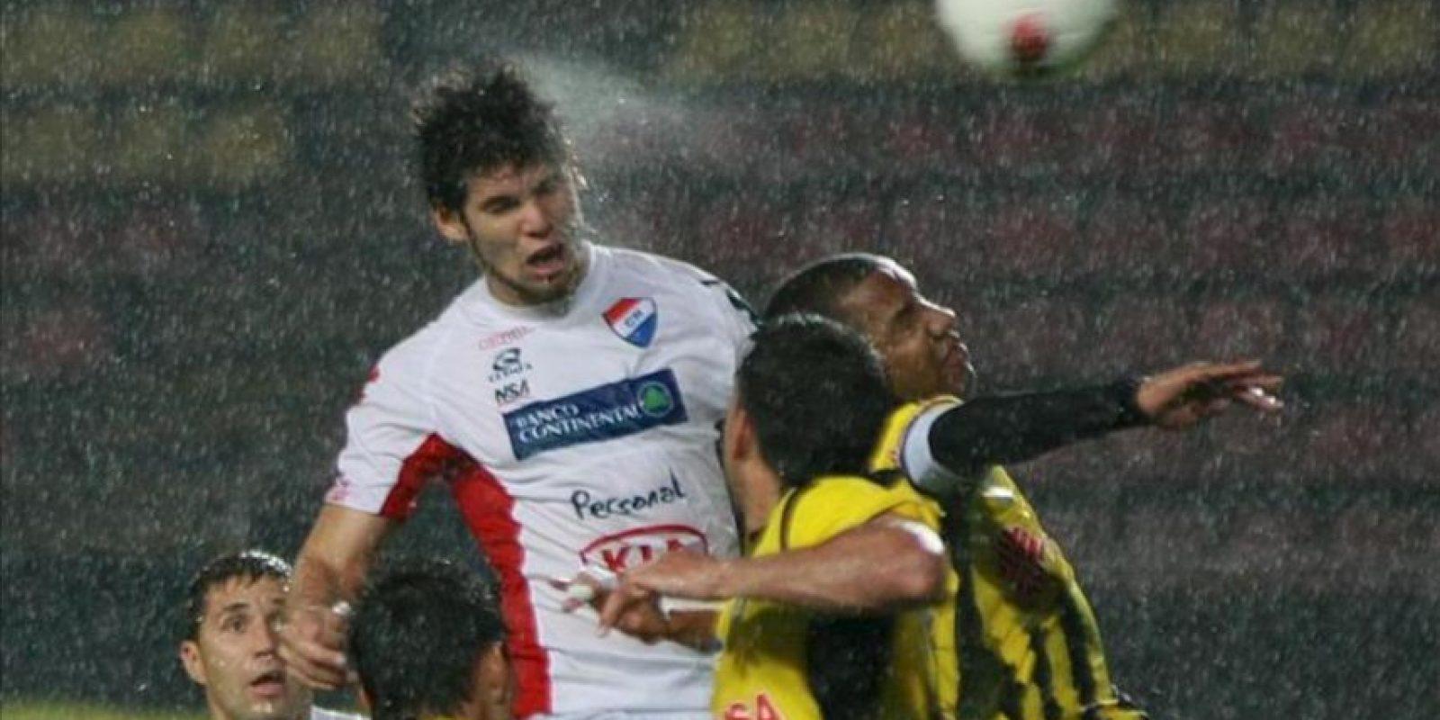 El jugador Ariel Bogado (cent) del equipo Nacional de Paraguay, disputa el balón con jugadores del Deportivo Táchira de Venezuela, durante el partido de la Copa Libertadores en el estadio de Pueblo Nuevo en San Cristobal (Venezuela). EFE