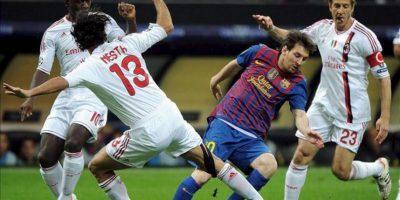 El jugador del AC Milán, Alessandro Nesta (13), pelea por el control del balón con el delantero argentino del FC Barcelona, Lionel Messi, en el partido de ida de cuartos de final de la Liga de Campeones en el estadio Giuseppe Meazza de Milán, Italia. EFE