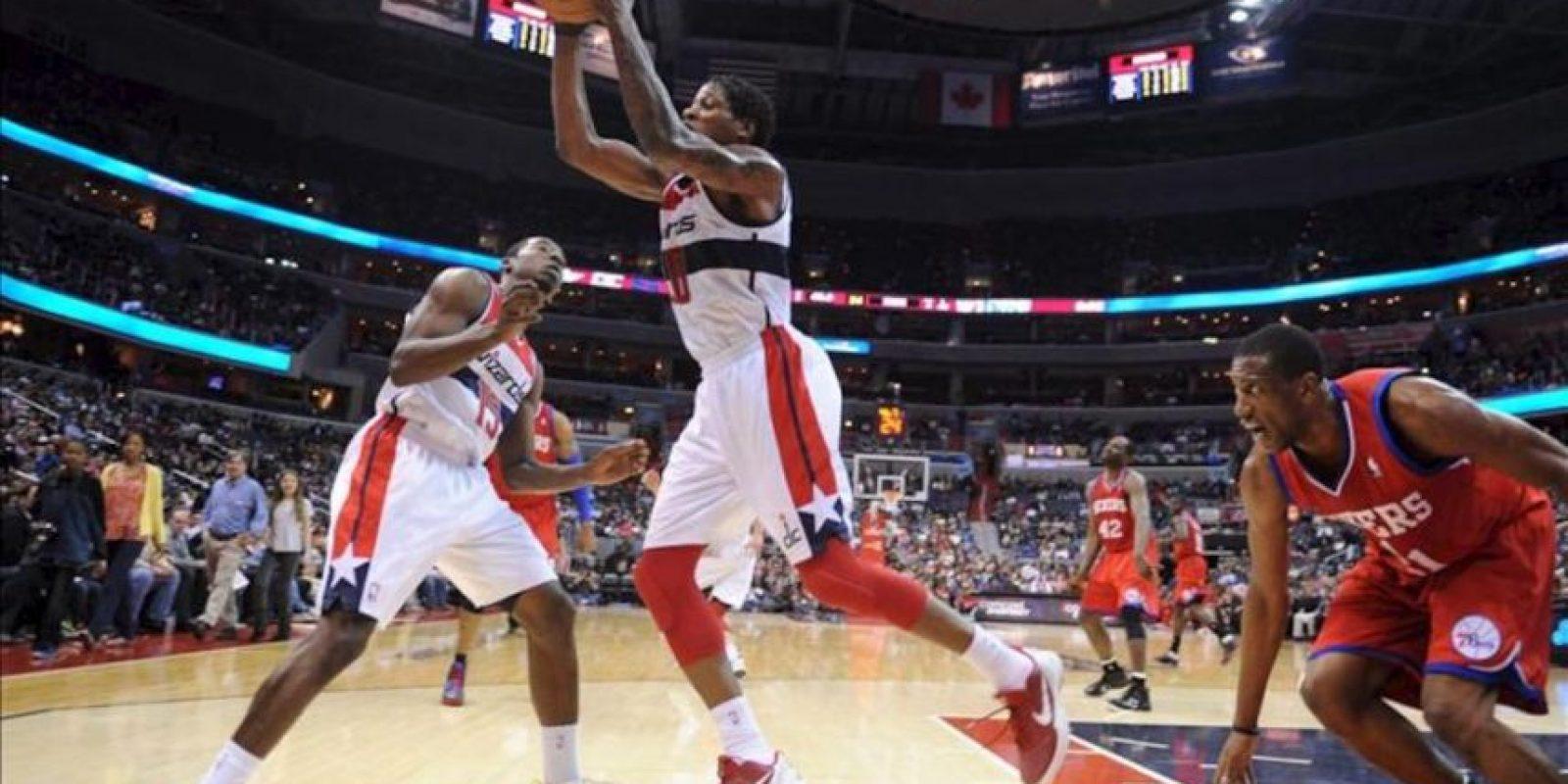 El jugador de Wizards Cartier Martin (c) alcanza un rebote ante la marca de Jrue Holiday (d), de Sixers, durante un partido por la NBA en el Verizon Center de Washington (DC, EE.UU.). EFE