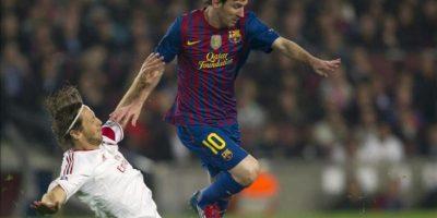 El delantero argentino del Barcelona Lionel Messi (d) intenta superar al jugador del Milán Massimo Ambrosini en el partido de vuelta de los cuartos de final de la Liga de Campeones en el Camp Nou. EFE