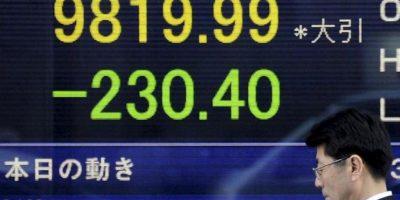 Un ejecutivo camina frente a un tablero electrónico que indica los resultados de la Bolsa de Tokio (Japón), donde el índice Nikkei cerró hoy con una caída de 230,40 puntos, el 2,29 por ciento, y quedó en 9.819,99 unidades. EFE