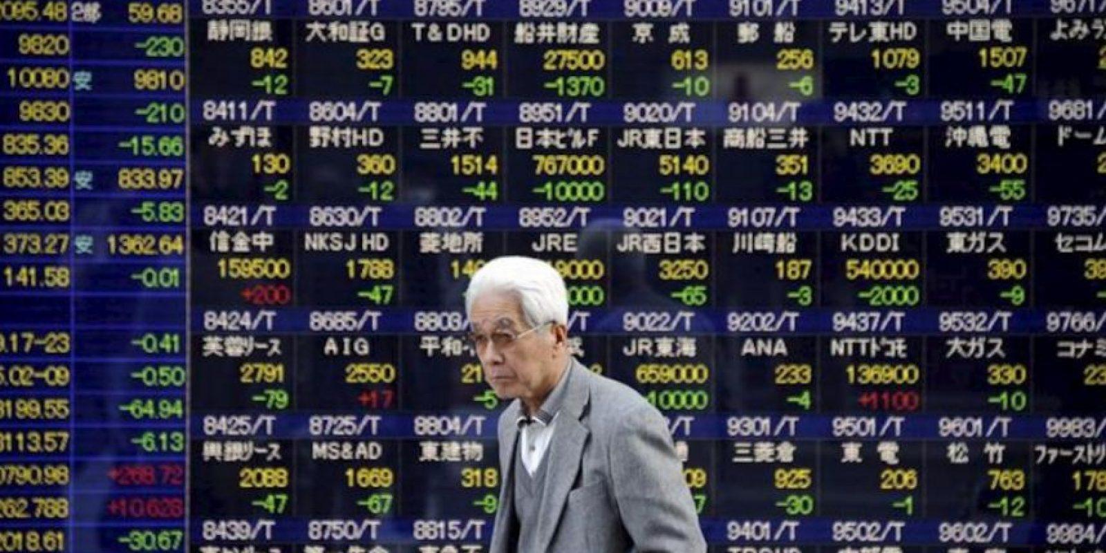 Un hombre camina frente a un tablero electrónico que indica los resultados de la Bolsa de Tokio (Japón), donde el índice Nikkei cerró hoy con una caída de 230,40 puntos, el 2,29 por ciento, y quedó en 9.819,99 unidades. EFE