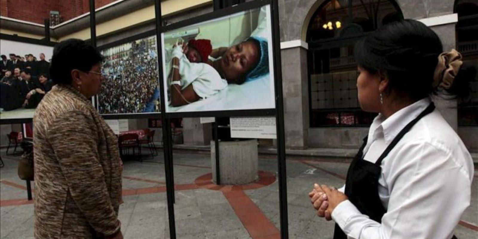 """Una mujer observa fotografías en el Centro Cultural Metropolitano de Quito (Ecuador), durante la muestra """"La Agencia Efe: El mundo en el 2011"""", la cual recoge las 82 mejores instantáneas del año pasado, tomadas en todo el planeta por sus fotoperiodistas. EFE"""