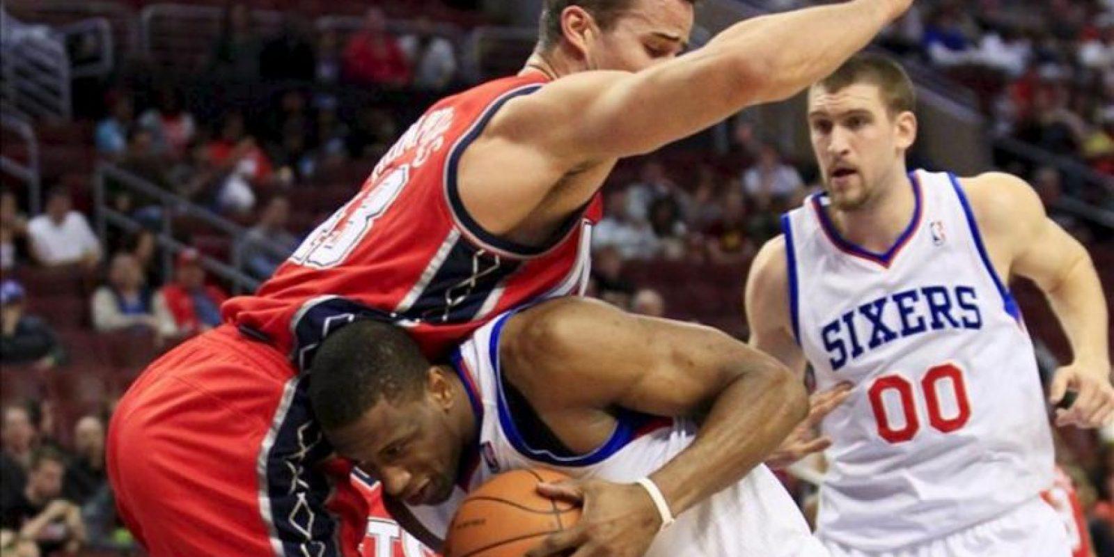 El jugador Thaddeus Young (c) de Philadelphia 76ers choca con Kris Humphries (d) de New Jersey Nets disputa un balón con Spencer Hawes (d) durante un juego de la NBA en el Centro Wells Fargo en Philadelphia (EEUU). EFE