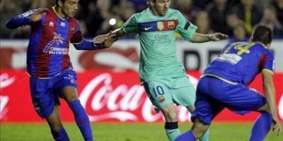 El delantero argentino del FC Barcelona Lionel Messi (c) conduce el balón ante los jugadores del Levante UD Gustavo Cabral (i) y Xavi Torres durante el partido, correspondiente a la trigésimo cuarta jornada de Liga de Primera División, que disputan ambos equipos en el estadio Ciudad de Valencia. EFE