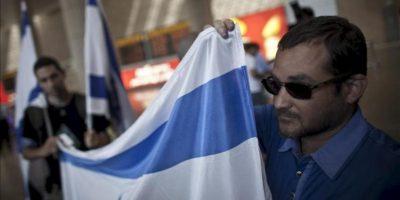 """Activistas israelíes de derechas reciben hoy a los turistas con banderas israelíes en el aeropuerto de Ben Gurion en Tel Aviv (Israel). Las autoridades israelíes han desplegado cientos de policías fronterizos para evitar la llegada de turistas bajo el reclamo de """"Bienvenido a Palestina"""". EFE"""