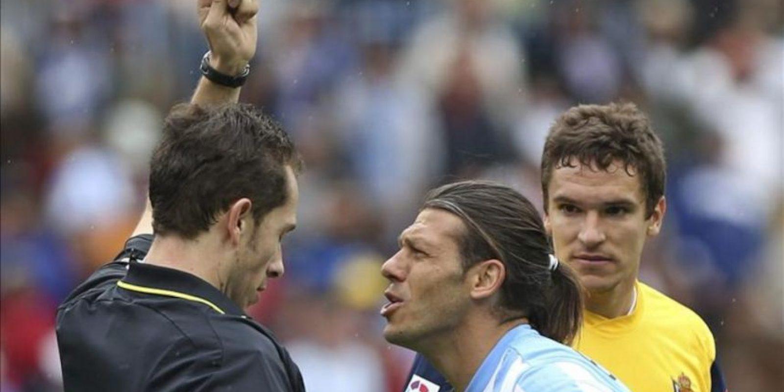 El defensa italo argentino del Málaga Martín Demichelis (c) recibe una tarjetya amarilla durante el partido, correspondiente a la trigésimo cuarta jornada de la Liga de Primera División, que disputó el conjunto andaluz ante la Real Sociedad en el estadio de La Rosaleda. EFE