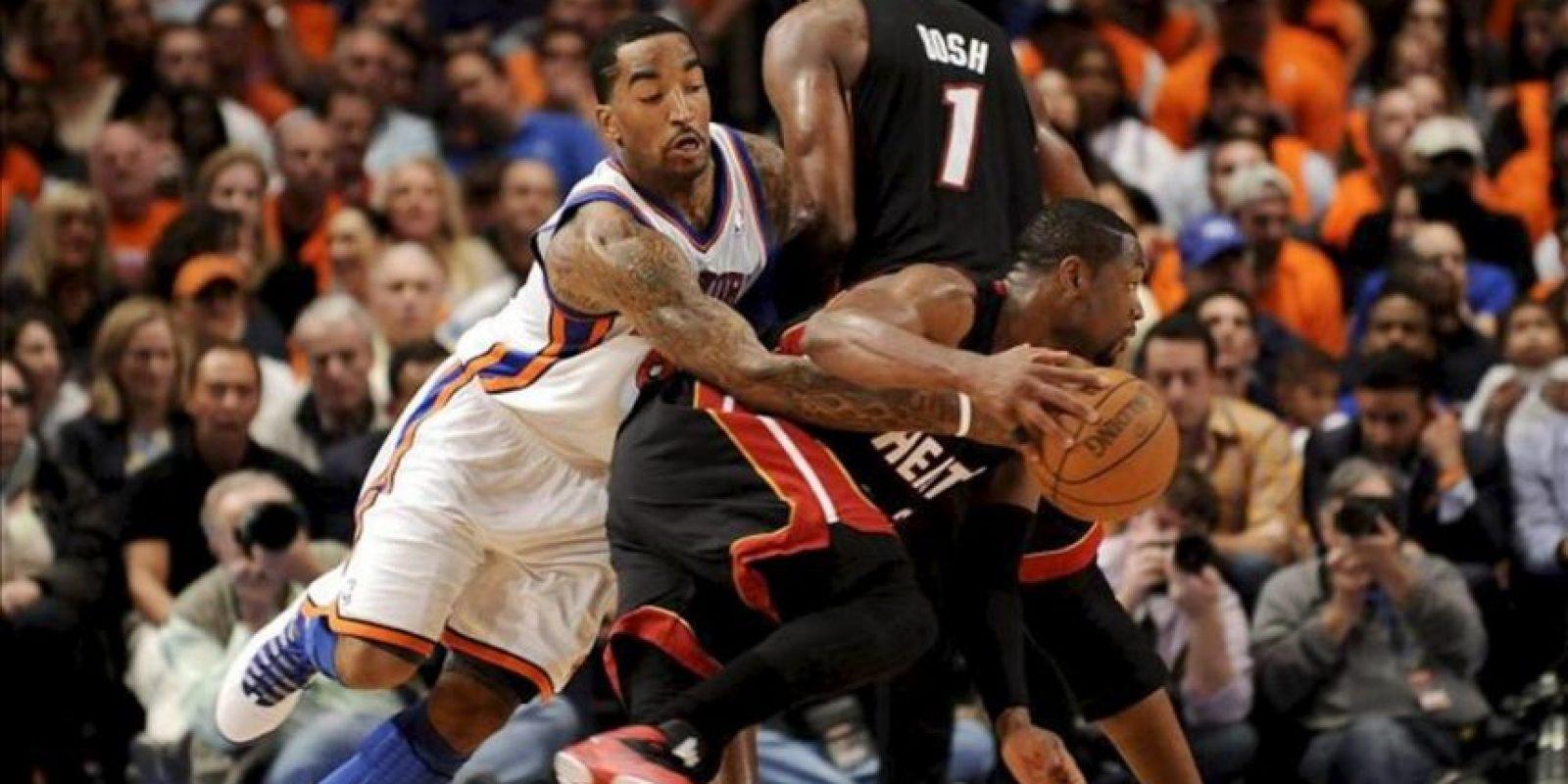 El jugador de los Knicks J.R. Smith (d) disputa un balón con Dwyane Wade (d) y Chris Bosh (c), de los Heat de Miami, durante un partido de la NBA, en el Madison Square Gerden de Nueva York (EEUU). Los Heat ganaron 93-85. EFE