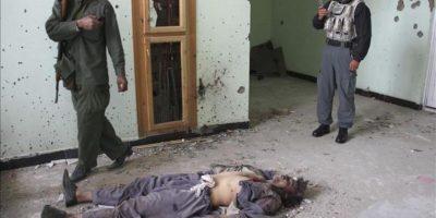 Agentes de la fuerza de seguridad afgana comprueban el cadáver de un supuesto talibán en el interior de un edificio que fue objeto de uno de los ataques coordinados lanzados por comandos talibanes, en Kabul, hoy, lunes 16 de abril de 2012. EFE