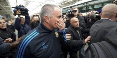 El entrenador del Real Madrid, Jose Mourinho (2-izq), rodeado de aficionados y periodistas al llegar al aeropuerto de Munich, Alemania para jugar el partido de ida de las semifinales de la Liga de Campeones el 17 de abril de 2012. EFE