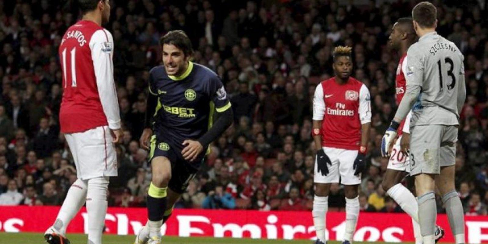 El jugador del Wigan Athletic Jordi Gomez (2-izq) celebra su gol al Arsenal (0-2) ante la presencia de los jugadores locales Andre Santos (izq), Alex Song (c), Johan Djourou (2-dcha) y Wojciech Szczesny (dcha), durante el partido de la Premier League que los dos equipos jugaron en el Emirates Stadium de Londres, Reino Unido. EFE