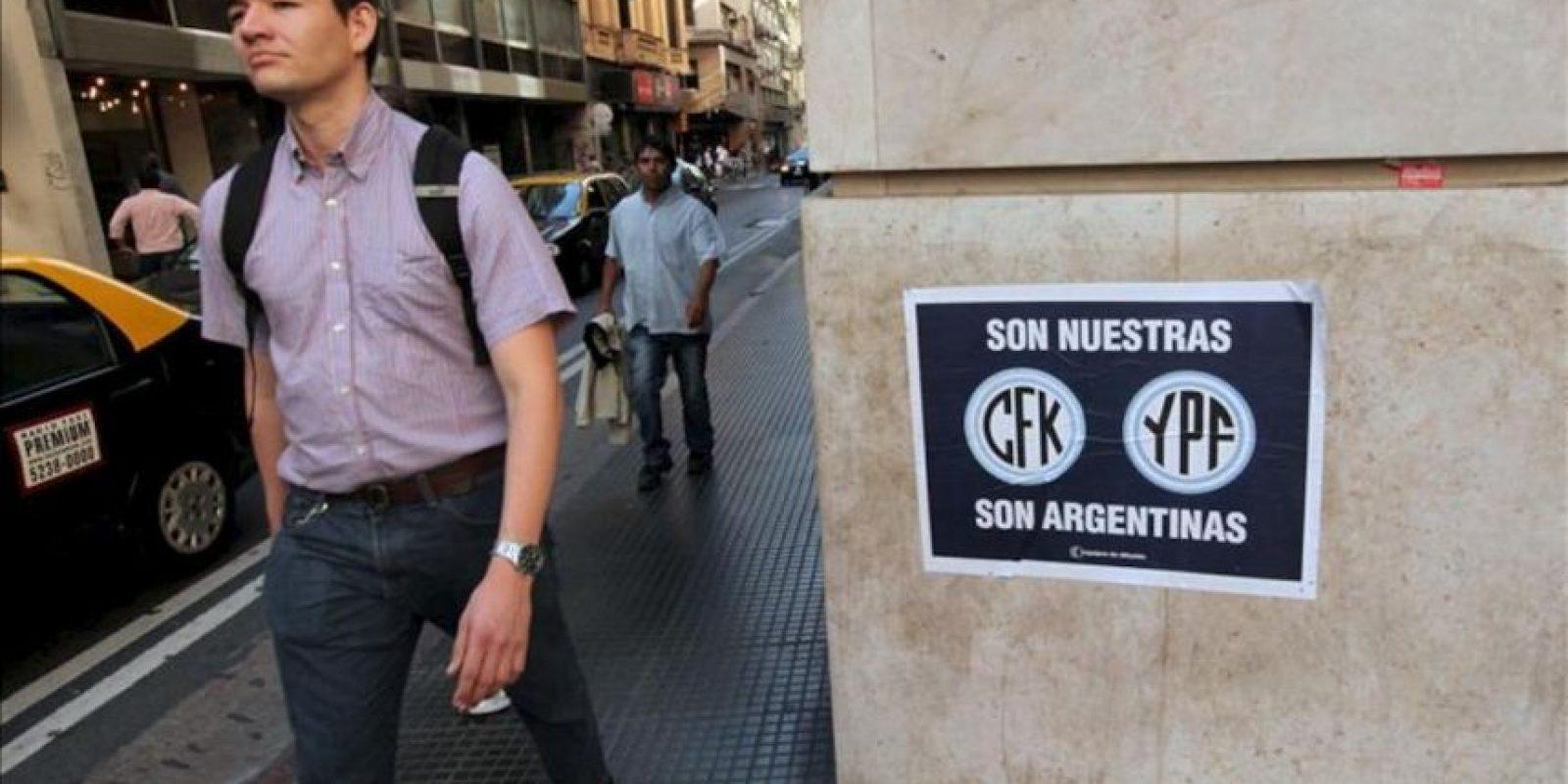 Un hombre camina junto a un afiche que hace referencia a la nacionalización de la petrolera YPF, este miércoles, en Buenos Aires (Argentina). EFE