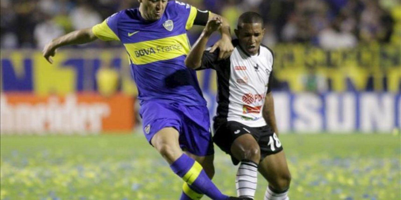 El jugador Juan Roman Riquelme (i) de Boca Juniors, lucha por el balón con Oscar Noriega (d) de Zamora, en un partido por la segunda fase del grupo cuatro de la Copa Libertadores 2012 en el estadio Diego J. Armando mas conocido como la Bombonera. EFE