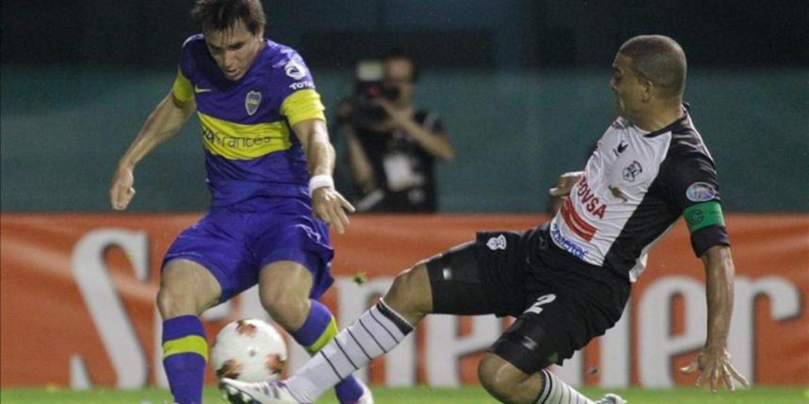 El jugador Pablo Mouche (i) de Boca Juniors, lucha por el balón con Moises Galezo (d) de Zamora, en un partido por la segunda fase del grupo cuatro de la Copa Libertadores 2012 en el estadio Diego J. Armando mas conocido como la Bombonera. EFE