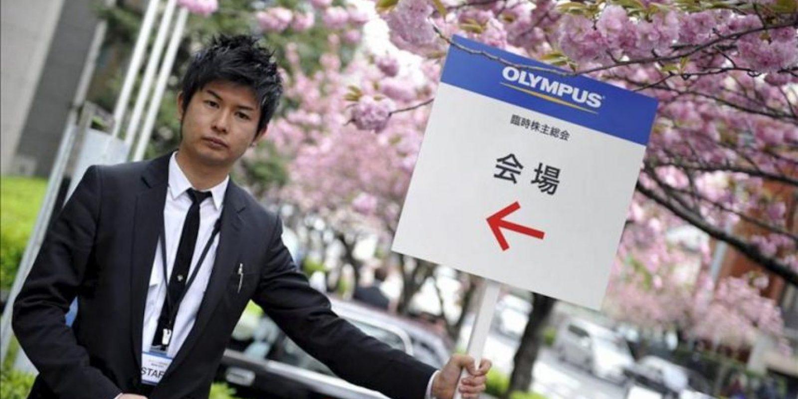 Un hombre sostiene un cartel que indica la ubicación de la reunión de accionistas de Olympus hoy, viernes 20 de abril de 2012, en Tokio (Japón). La reunión se lleva a cabo meses después de un escándalo de fraude al interior de la compañía. EFE