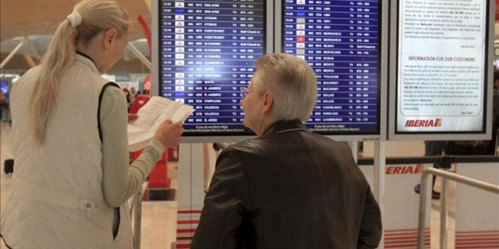 Dos personas consultan sus vuelos hoy, 20 de abril de 2012, en el aeropuerto de Madrid-Barajas, donde Iberia ha cancelado 120 vuelos, entre ellos seis entre Madrid y ciudades latinoamericanas, debido a la nueva jornada de huelga del sindicato de pilotos Sepla en protesta por la creación de la filial de bajo coste Iberia Express. EFE