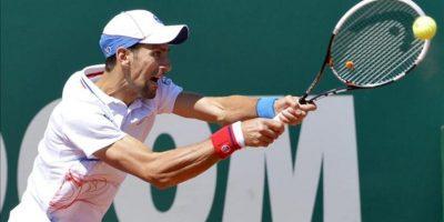El tenista serbio Novak Djokovic le devuelve hoy una bola al holandés Robin Haase durante el partido de cuartos de final del Masters 1.000 de Montecarlo, Francia. Novak Djokovic, con un juego muy irregular, se impuso al holandés Tommy Haase por 6-4 y 6-2. EFE