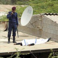 Un policía armado (i) custodia en un tejado el cuerpo del manifestante fallecido por disparos de la policía en la localidad de Shakura, al norte de Manamá (Baréin). EFE