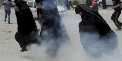 Mujeres corren para ponerse a cubierto mientras policías bareiníes lanzan gas lacrimógeno a los manifestantes durante unos disturbios en la villa de Shakura al norte de Manama en Baréin. EFE