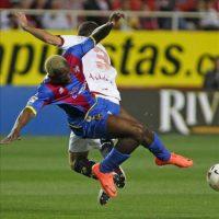 El delantero marfileño del Levante UD Arouna Koné (i) cae ante el defensa del Sevilla FC Fernando Navarro durante el partido, correspondiente a la trigésimo quinta jornada de Liga de Primera División, que disputaron ambos equipos en el estadio Ramón Sánchez Pizjuán. EFE