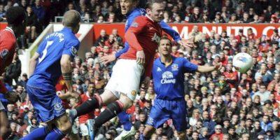 El futbolista del Manchester United Wayne Rooney (c) golpea el balón para marcar el gol del empate ante Heitinga (izq) y Phil Nevile (c, detrás) del Everton durante el partido de la Liga inglesa de fútbol disputado en el estadio Old Trafford en Manchester (Reino Unido). EFE